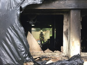 An NKF&R firefighter, visible through broken windows and doors, pauses from the hard work of digging through debris to snuff hotspots remaining after a fire of unknown origin destroyed a garage in Suquamish on Tuesday evening.