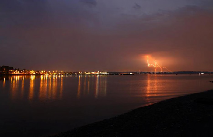 Kingston's port and ferry terminal are lit up across Apple Tree Cove as lightning strikes across Puget Sound.